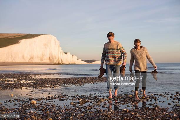 Couple walking bare foot on beach