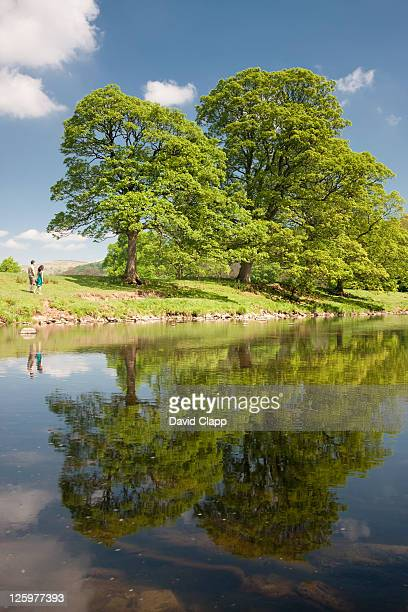 Couple walking beside the River Hodder in the Forest of Bowland, Lancashire, England, UK