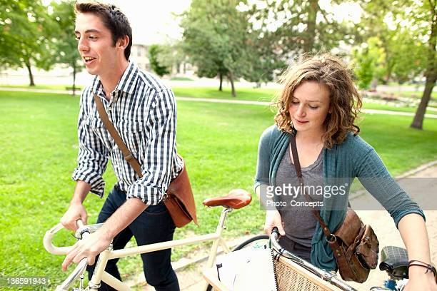 couple walking bikes in park - peterborough ontario stock photos and pictures