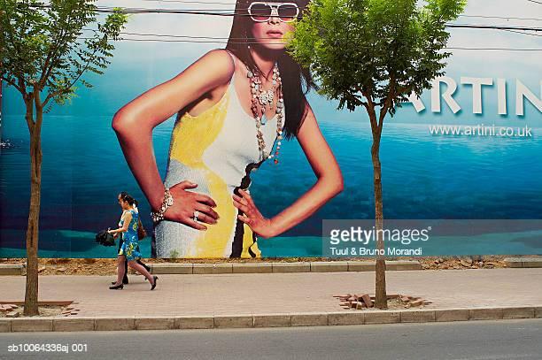 Couple walking by large billboard in street
