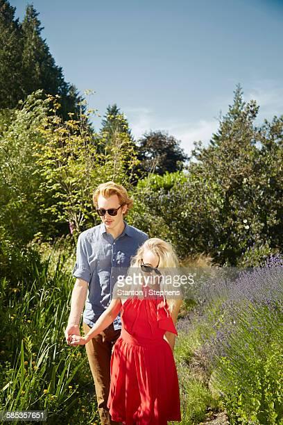 Couple walking by lavender in garden, Seattle, Washington, USA