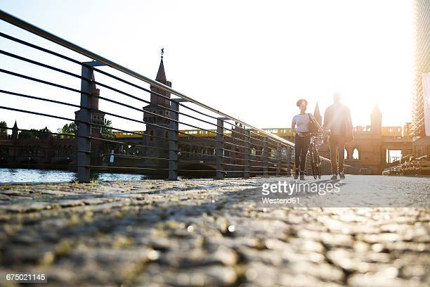 couple walking by river, pushing bicycle - spree river stock pictures, royalty-free photos & images