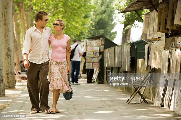 Couple walking by street market, smiling at each other