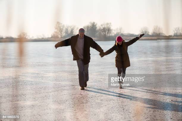 Couple walking carefully on frozen lake
