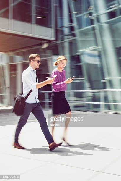 Couple Walking Discussing  and Using Portable Devices