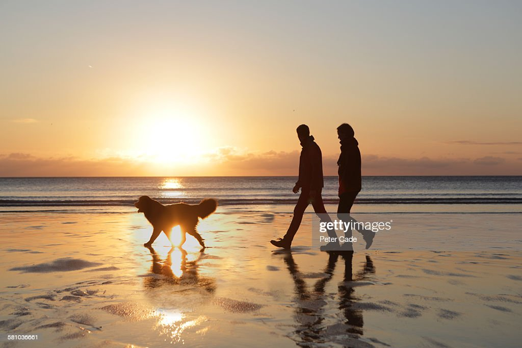 Couple walking do on beach at sunset : Stock Photo
