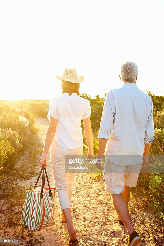 Couple walking down a pathway among shrubs : Stock Photo