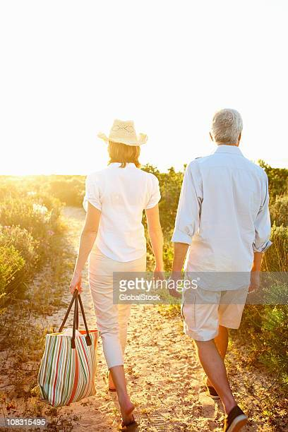 Couple walking down a pathway among shrubs