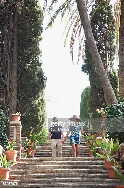 couple walking down staircase outdoors - tropical tree stockfoto's en -beelden