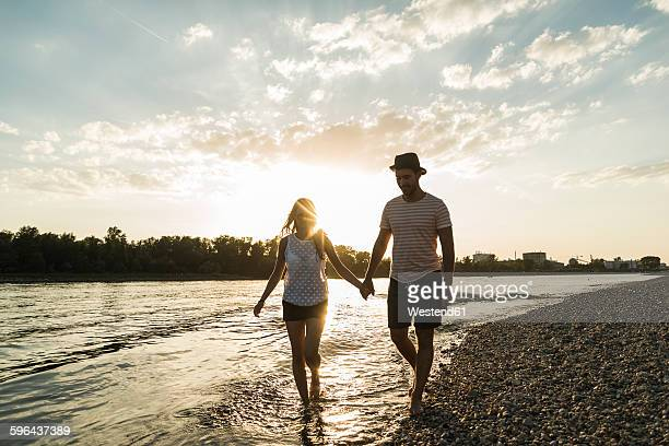 Couple walking hand in hand at the riverside at sunset