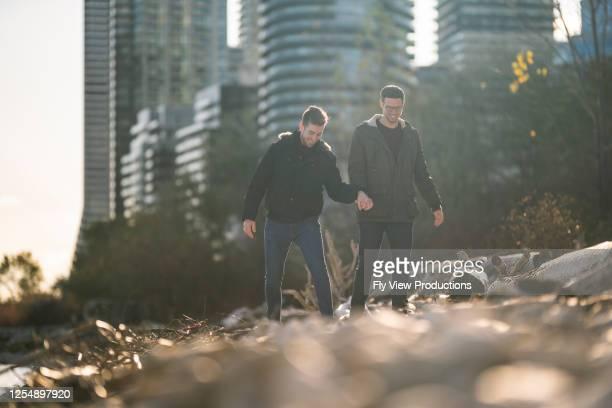 街の近くの公園で手をつないで歩くカップル - ゲイ ストックフォトと画像