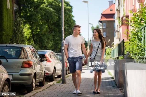 Couple walking hand in hand on sidewalk