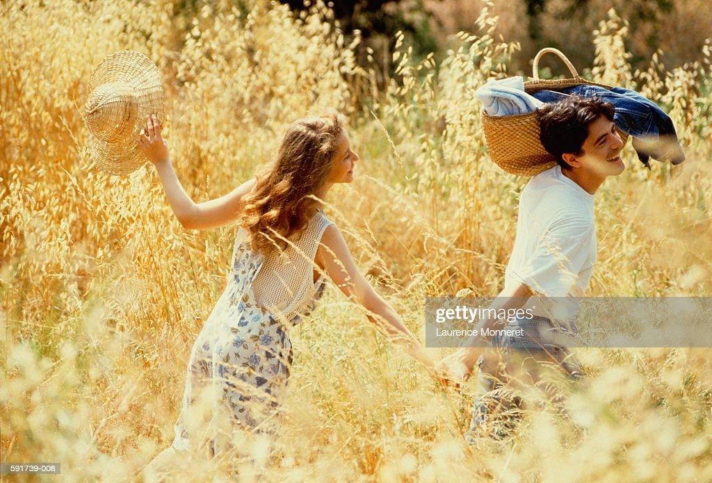 Couple walking hand in hand through field,man with basket on shoulder : Foto de stock