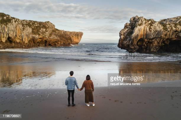 couple walking holding hands on the beach - llanes fotografías e imágenes de stock