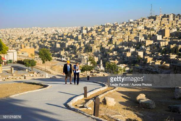 Couple walking in Amman Citadel with city of Amman in background, Capital Governorate, Jordan
