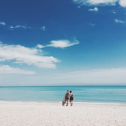 Couple Walking In Arm Around At Beach Against Sky - gettyimageskorea