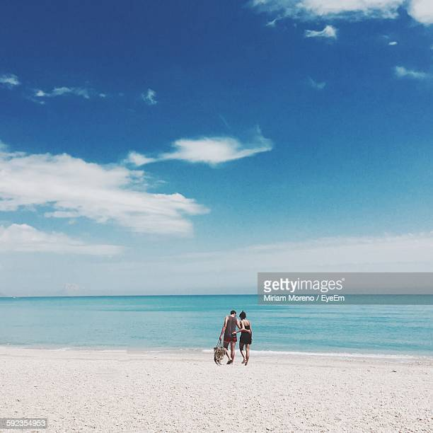 Couple Walking In Arm Around At Beach Against Sky