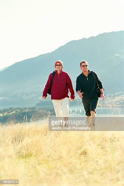 couple walking in countryside - wasserform stock-fotos und bilder