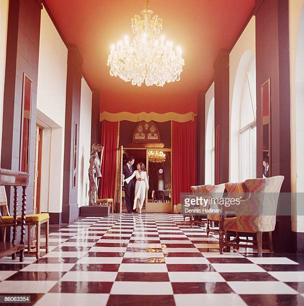 Couple walking in hallway of mansion