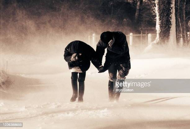 A couple walking in high winds on a snowy day at Stoven Suffolk England January 1997