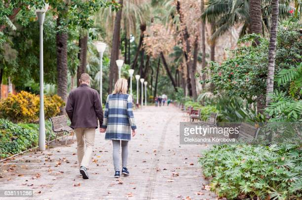 Couple walking in lush green tropical gardens in Malaga, Andalusia, Spain