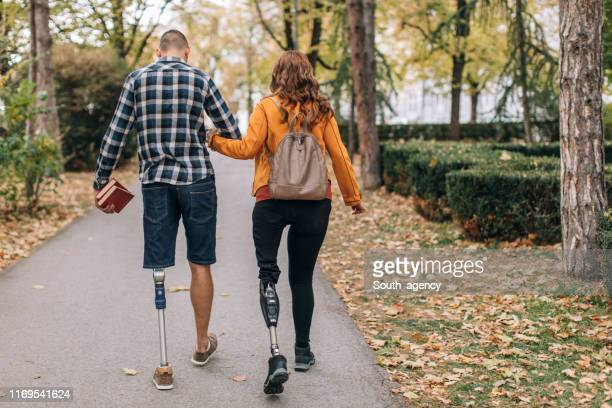 couple walking in park - amputee woman stock pictures, royalty-free photos & images