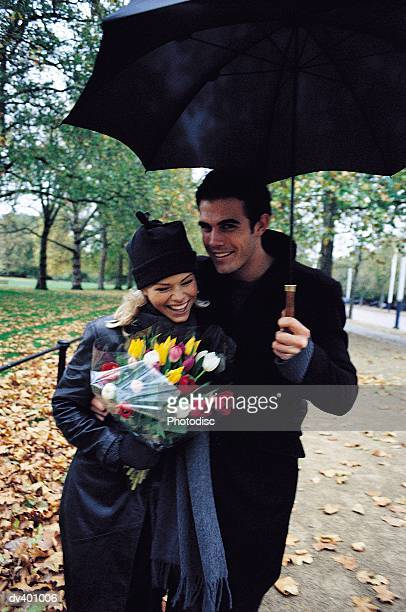 Couple walking in park with umbrella and bouquet