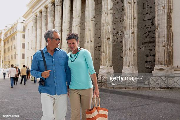 Couple walking in Piazza di Pietra, Italy
