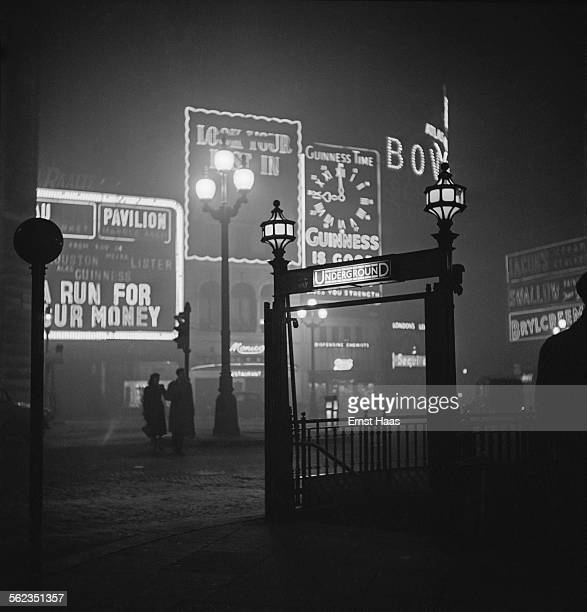 A couple walking in Piccadilly Circus at night London circa 1953