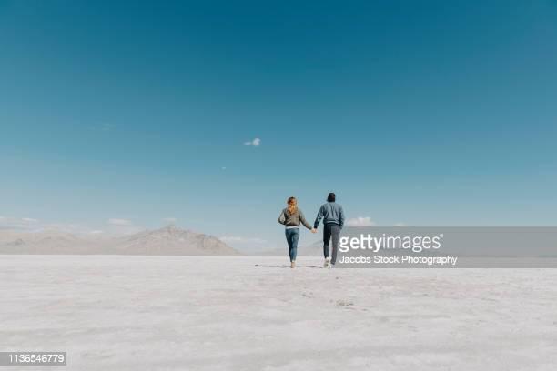 couple walking in remote landscape - bonneville salt flats stock pictures, royalty-free photos & images