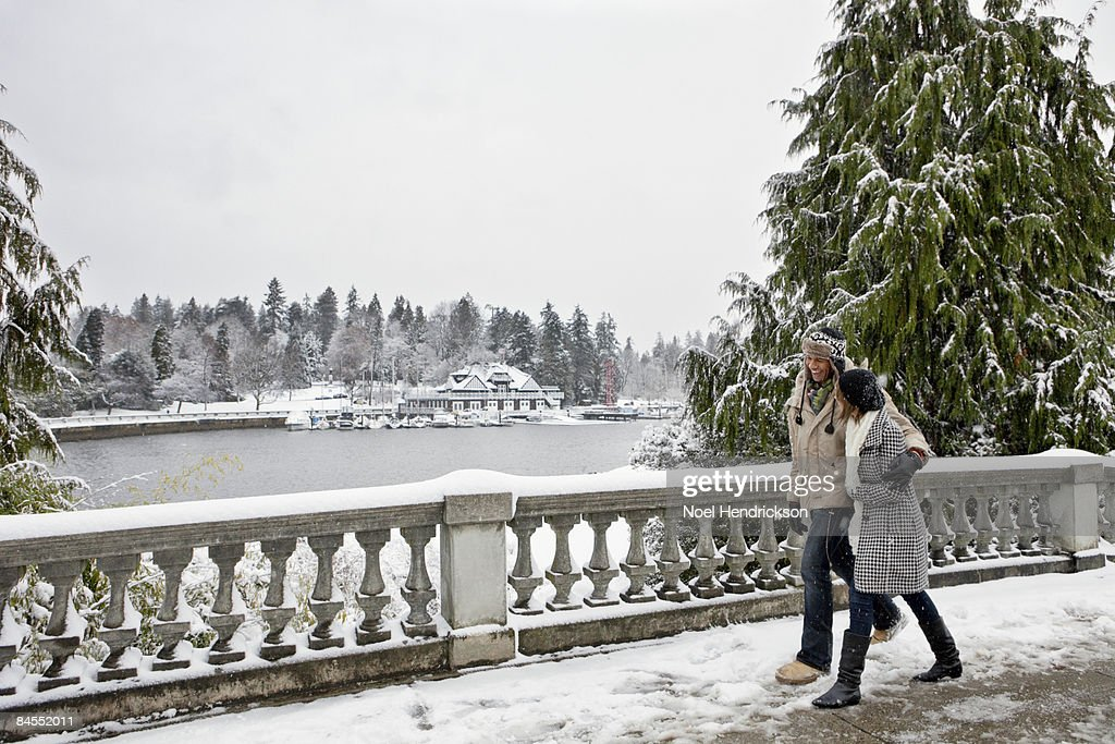 couple walking in snow covered urban park : Stock Photo