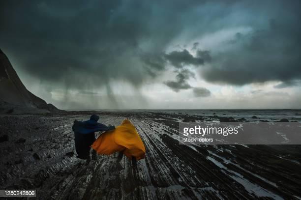 pareja caminando en tiempo tormentoso - primavera estación fotografías e imágenes de stock