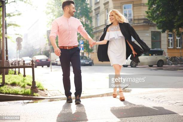 Couple walking in street holding hands