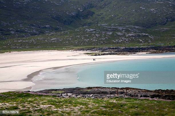 Couple walking in the distance on sandy beach in Halaman bay, Barra, Outer Hebrides, Scotland.