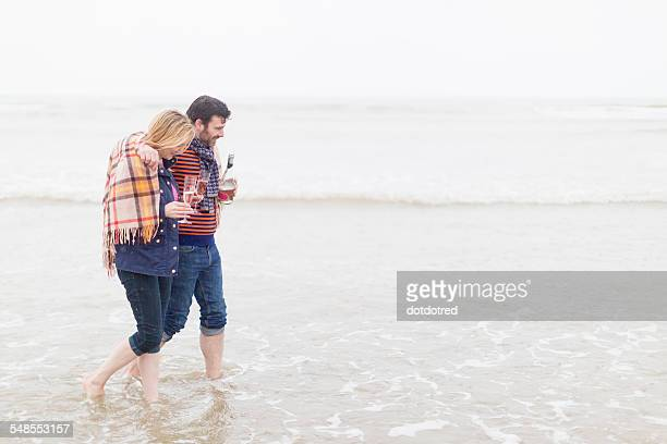 Couple walking in the sea, holding wine and wine glasses