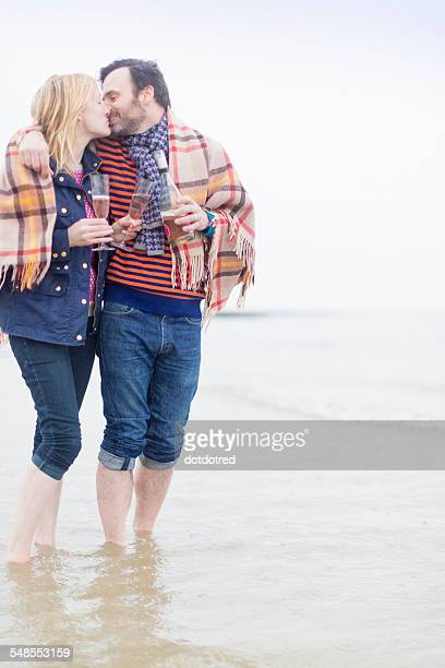 Couple walking in the sea, kissing, holding wine and wine glasses