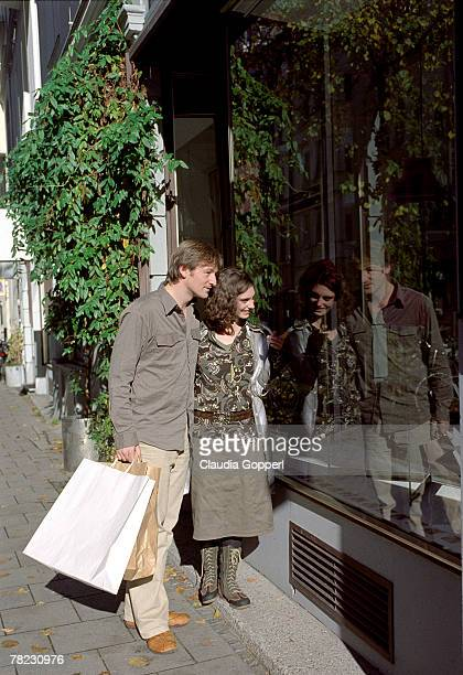 couple walking in the street looking at shop window