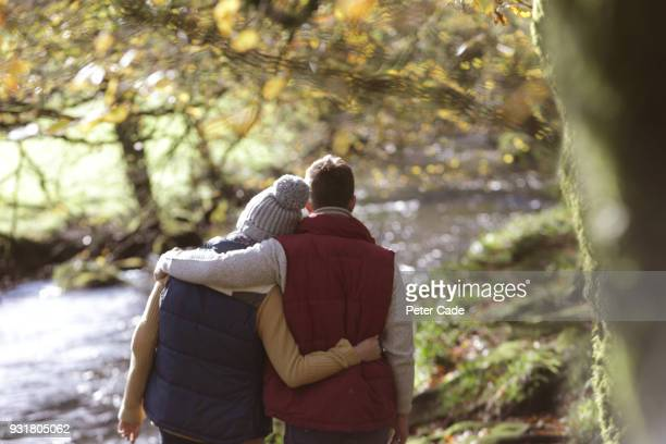 couple walking in woodland next to river - 死を悼む ストックフォトと画像