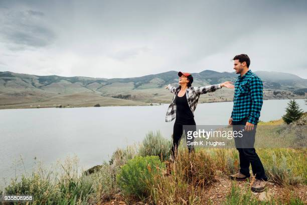 couple walking near dillon reservoir, young womans arms outstretched, silverthorne, colorado, usa - 近く ストックフォトと画像
