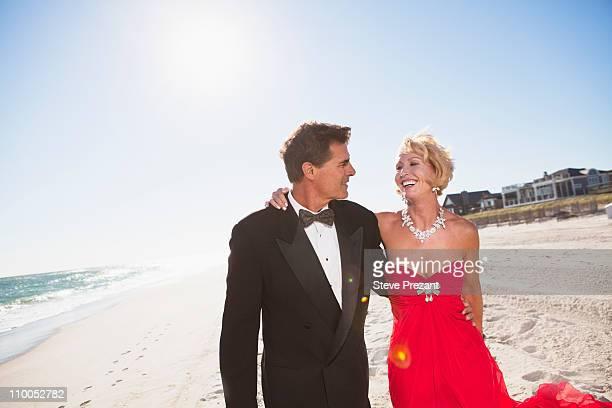 couple walking on a beach - white tuxedo stock pictures, royalty-free photos & images