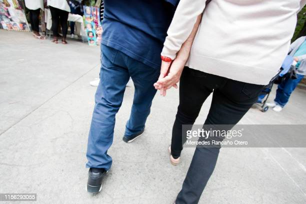 couple walking on a city street sidewalk, holding hands. - pedestrian zone stock pictures, royalty-free photos & images