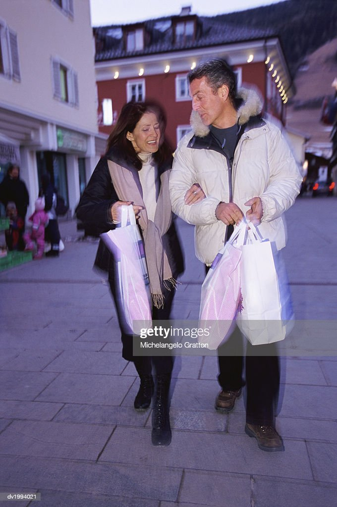 Couple Walking on a Pavement in Town Carrying Shopping Bags : Stock Photo
