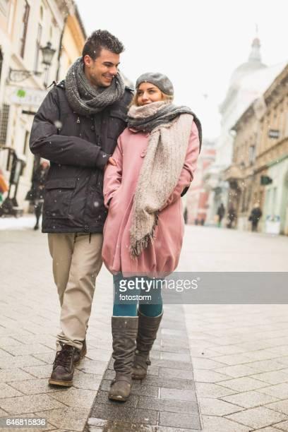Paare, die auf einer verschneiten Stadt Straße