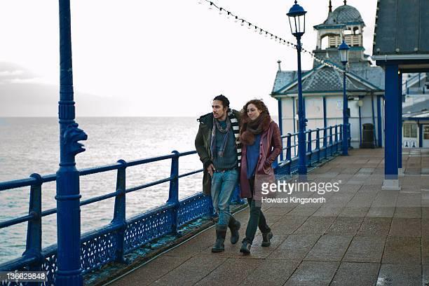 couple walking on a windswept pier in winter