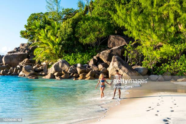 couple walking on anse georgette beach - indian ocean stock pictures, royalty-free photos & images