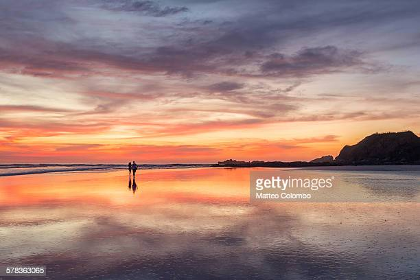 Couple walking on beach at sunset, Costa Rica