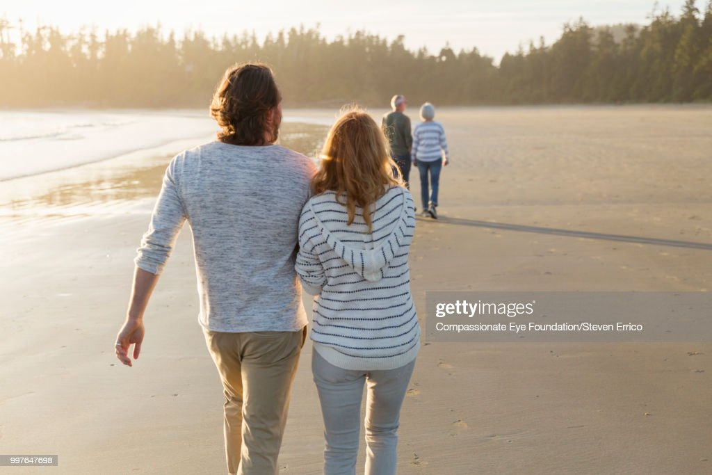 Couple walking on beach at sunset : Stock Photo