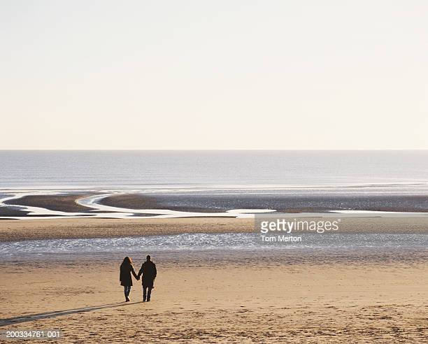 couple walking on beach, holding hands, rear view - camber sands stock photos and pictures