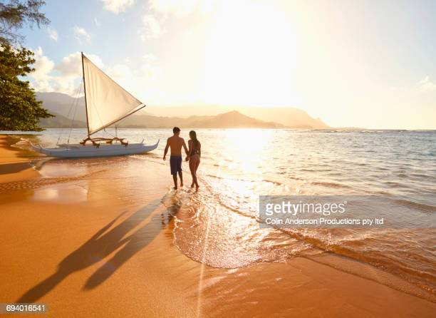 Couple walking on beach near sailboat