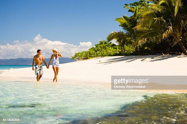 couple walking on beach - fiji stock pictures, royalty-free photos & images
